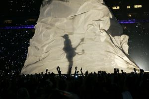 "Prince is shown in silhouette as he performs during the halftime show at the Super Bowl XLI football game at Dolphin Stadium in Miami on Sunday, Feb. 4, 2007. Prince's acclaimed performance included a guitar solo during the ""Purple Rain"" segment of his medley in which his shadow was projected onto a large, flowing beige sheet. (AP Photo/Alex Brandon)"